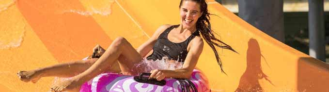 pretty woman on the rubber ring having fun on the orange water slide in the aqua park. Summer Vacation. Weekend on resort