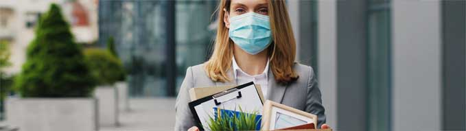 Portrait of Caucasian sad businesswoman in medical mask standing outdoor with box of stuff. Leaving business. Female office worker lost her job.