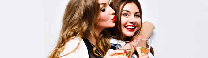 Close up funny portrait of pretty girls having fun on amazing party, bright make up, long hairs, holding glasses with champagne, pretty portrait of best friends, image with flash.