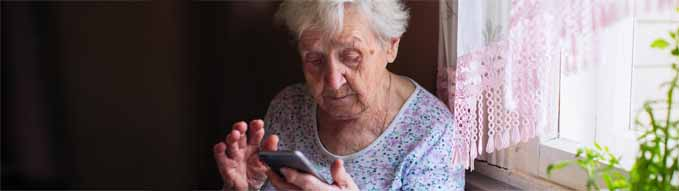 An old woman sits in home with a smartphone.