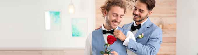 Happy newlywed gay couple with flower at home