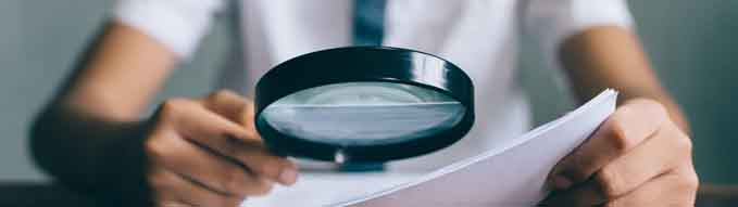 asian boy student looking at paper using magnifying glass. education concept