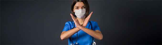 A young girl, doctor in a medical mask, in a blue suit and with a stethoscope, shows with her hands the gesture: ban, stop, closed,  prohibited.