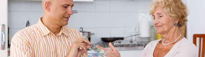 Senior woman giving money to her son at kitchen table