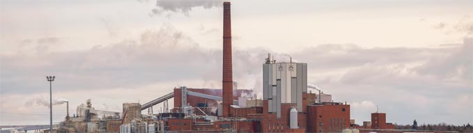 KOTKA, FINLAND - NOVEMBER 02, 2019: Sunila pulp and paper mill of Stora Enso Oyj corporation on shore of Gulf of Finland. Red brick industrial buildings and smoking chimneys